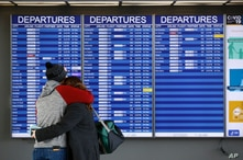 A man and woman embrace in front of a flight departures board at Dulles International Airport in Dulles, Va., Tuesday, March 17…