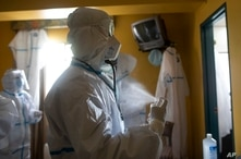 A doctor sprays himself with alcohol after checking on asymptomatic COVID-19 patients quarantining at a hotel, before removing…