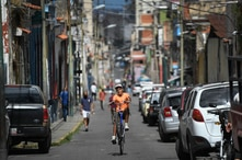 A youth pops a wheelie as he rides through the streets of La Pastora neighborhood of Caracas, Venezuela, Saturday, Aug. 22,…