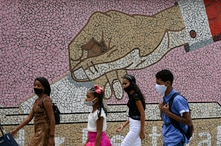 Youths wearing masks against the spread of the new coronavirus, walk past a mosaic mural with the image of a hand depositing a…