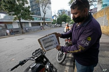 "A moto-taxi driver, wearing a face mask amid the new coronavirus pandemic, places a price sign that reads in Spanish ""Minimum 1…"