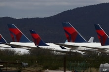 Tail fins of recently landed Delta Air Lines sit parked at Pinal Airpark Wednesday, March 18, 2020, in Red Rock, Ariz., as many…
