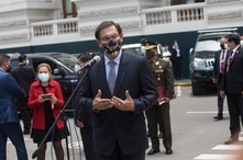 Wearing a mask amid the COVID-19 pandemic, Peruvian President Martin Vizcarra talks to reporters after leaving the Congress in…
