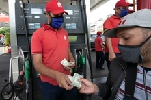 A customer pays with U.S. dollar bills before filling up his motorcycle at a gas station in Caracas, Venezuela, Monday, June 1,…