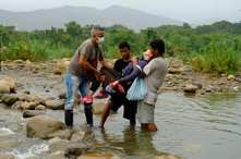 A Venezuelan woman is helped by men to cross illegally into Colombia from Venezuela, near the Simon Bolivar International…