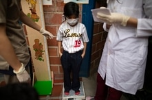 A child, wearing a face mask amid the new coronavirus, is weighed during a vaccination campaign organized by the Health…