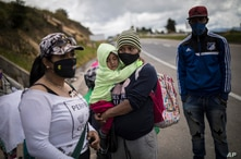 Venezuelan migrants rest as they walk towards Bogota, passing through Tunja, Colombia, Tuesday, Oct. 6, 2020. Immigration…