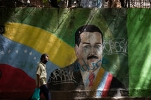 A man wearing a face mask amid the COVID-19 pandemic passes a mural of Venezuelan President Nicolas Maduro in Caracas,…