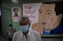 A man waits to cast his ballot in front of a mural of late President Hugo Chavez at a polling station during elections to…