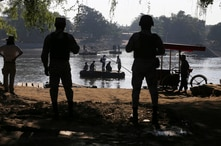 Mexican National Guards stand watch over the Suchiate River where locals transport cargo and ferry people between Mexico and…