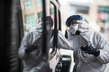 A passenger gets swabbed for COVID-19 at a testing site at the convention center in Providence, R.I, Tuesday, Dec. 1, 2020. (AP…
