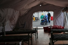 A person who tested positive for the new coronavirus is transferred to one of the tents set up outside the Seguro Social…