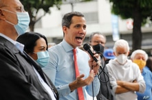 Flanked by party members, Venezuelan opposition leader Juan Guaido speaks during a press conference, a day after parliamentary…