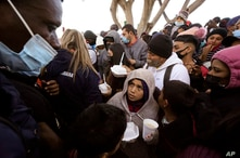 Asylum seekers receive food as they wait for news of policy changes at the border, Friday, Feb. 19, 2021, in Tijuana, Mexico…