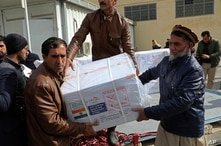 FILE - In this file photo dated Sunday, Feb. 7, 2021, Afghan health ministry workers unload boxes of the first shipment of 500…
