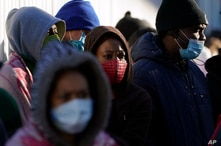 Asylum seekers wait for news of policy changes at the border, Friday, Feb. 19, 2021, in Tijuana, Mexico. After waiting months…