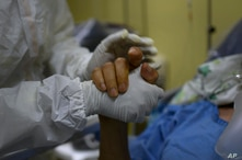 A health worker takes the hand of COVID-19 patient at the intensive care unit of the Ana Francisca Perez de Leon II public…