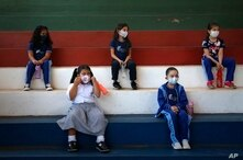 First graders, wearing protective face masks, sit to maintain a social distance in a gym during class at the San Juan Bautista…