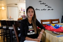 "Mariana Molero wears a ""TPS for Venezuelans"" T-shirt as she poses for a photo at her home in Pembroke Pines, Fla., Friday, Jan…"