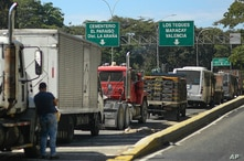 Truck drivers line up along the side of the road to fill up their tanks with diesel during a fuel shortage in Caracas,…