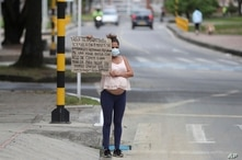 Venezuelan migrant Veronica Hernandez, 20, who is eight months pregnant, holds up a sign with a handwritten message asking for…