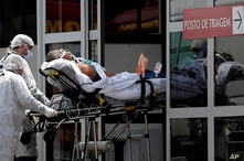 Healthcare workers take on a stretcher a patient suspected of having COVID-19 from an ambulance into the HRAN public hospital…
