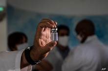 A doctor shows an empty vial of the experimental Soberana 02 vaccine for COVID-19 being developed at the Molecular Immunity…