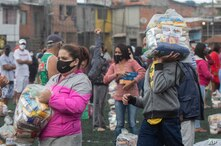 """Residents socially distance on a soccer field as they stand with bags of food donated by the local NGO """"G10 Favelas,"""" amid the…"""