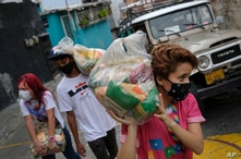 Youth carry bags of basic food staples, such as pasta, sugar, flour and kitchen oil, provided by a government food assistance…