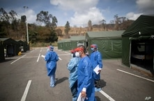 HEalth workers walk in a field hospital set up on the parking lot of the Poliedro de Caracas auditorium, in Venezuela, Sunday,…