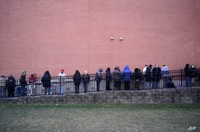 People wait in line for the COVID-19 vaccine in Paterson, N.J., Thursday, Jan. 21, 2021. The first people arrived around 2:30 a…
