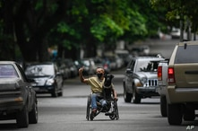 A man wearing a mask to curb the spread of the new coronavirus, carries his dog on his wheelchair, asking for handouts from…