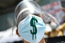 A healthcare worker wearing a protective shield and a face mask marked with a dollar sign in support of dollarization, takes…