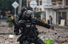 A police officer winds up to throw a stun grenade at protesters during a national strike against tax reform in Cali, Colombia,…