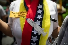A nurse wears a scarf designed with colors that represent the Venezuelan national flag, and a cutout depicting a syringe,…