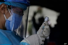 A healthcare worker prepares a dose of the AstraZeneca vaccine for COVID-19 at the Epiclachima Military Fort where soldiers are…