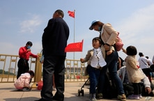 A child holds a Chinese national flag during a visit to Tiananmen Square for the May Day holidays in Beijing on Monday, May 3,…