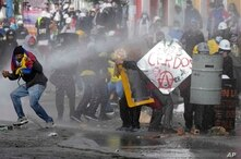 Demonstrators cover themselves from a police water cannon with makeshift shields during continuing anti-government protests…