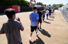 Children walk together after a game of soccer at an emergency shelter for migrant children Friday, July 2, 2021, in Pomona,…