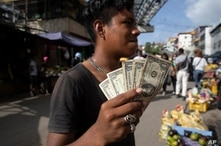 A young man flashes his one dollar US bills at a street market in Caracas, Venezuela, Friday, June 11, 2021. ( AP Photo/Ariana…