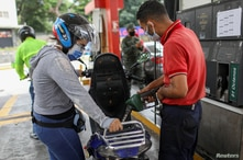 Marlene de Abreu refills gasoline in her motorbike at a gas station in Caracas