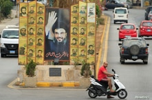 A man rides a motorbike past a poster depicting Lebanon's Hezbollah leader Sayyed Hassan Nasrallah