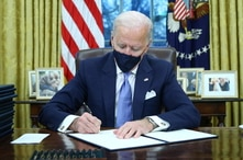 President Joe Biden signs executive orders inside the Oval Office at the White House in Washington