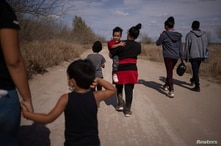 Migrant families walk down dirt road after crossing the Rio Grande River into thr U.S. from Mexico in Penitas, Texas