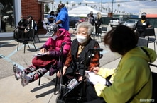People wait to receive a second coronavirus disease (COVID-19) vaccination, in Los Angeles