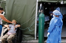 A doctor looks on while monitoring the progress of a patient who is suffering from the coronavirus disease (COVID-19) at the shock and trauma medical tent in the Poliedro de Caracas field hospital