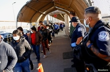 Migrants expelled from the U.S. and sent back to Mexico under Title 42 walk towards Mexico at the Paso del Norte International border bridge, in Ciudad Juarez