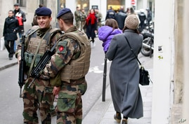 French army soldiers patrol near Rue des Rosiers street, in the heart of the Paris Jewish quarter, Monday Jan. 12, 2015. France on Monday ordered 10,000 troops into the streets to protect sensitive sites after three days of bloodshed and terror, amid the