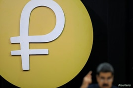 "The Venezuelan cryptocurrency ""Petro"" logo is seen as Venezuela's President Nicolas Maduro speaks during a meeting with the…"