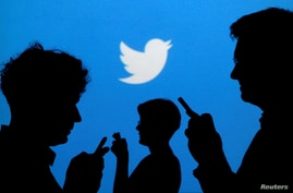 FILE PHOTO: People holding mobile phones are silhouetted against a backdrop projected with the Twitter logo in this…